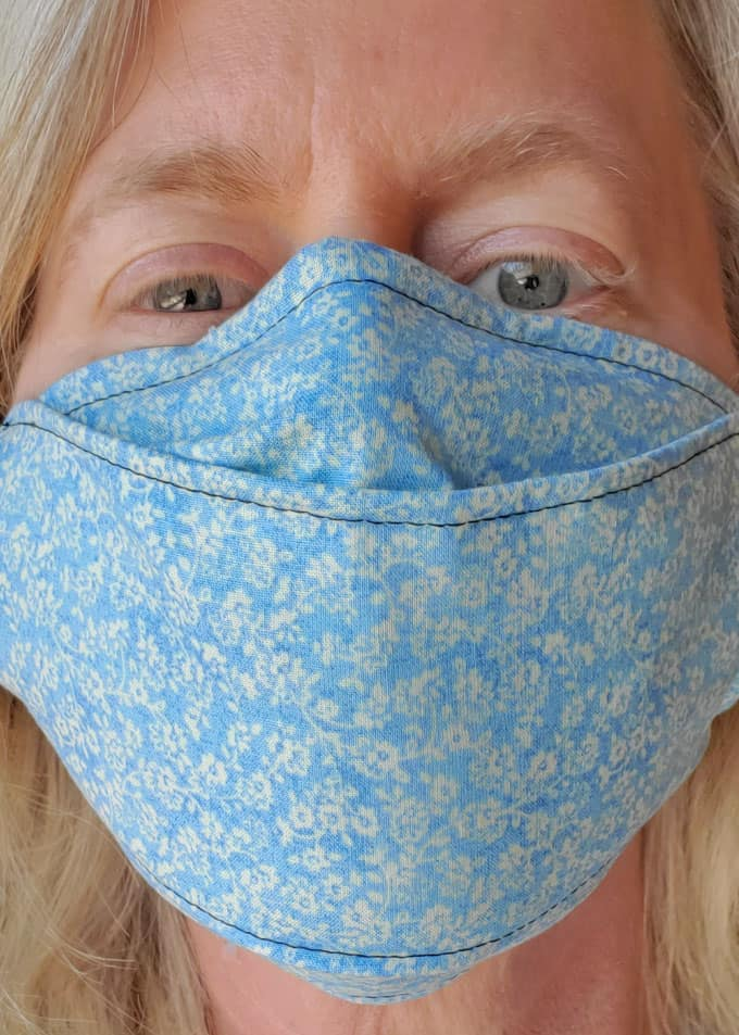 close up of a blue face mask on a woman