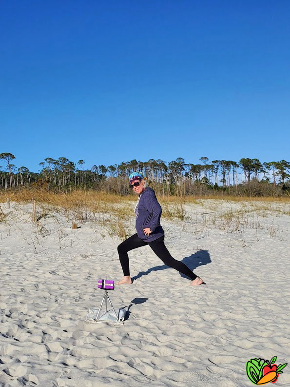 woman showing how a lunge on a beach is one of the best travel workouts