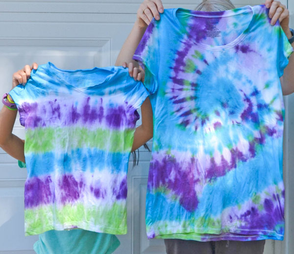 2 people holding up the tie-dye shirts they made