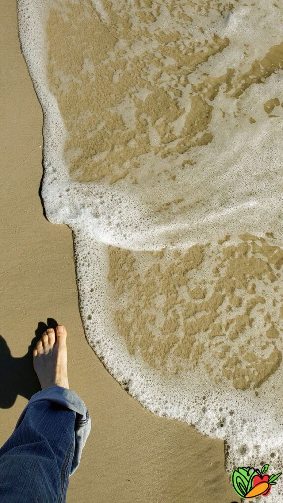 woman's foot walking on a beach