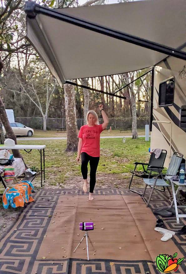 woman doing an exercise class at a campground next to an RV