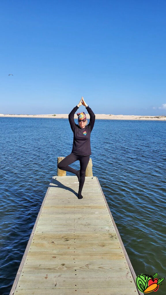 a woman taking yoga on a pier next to a harbor