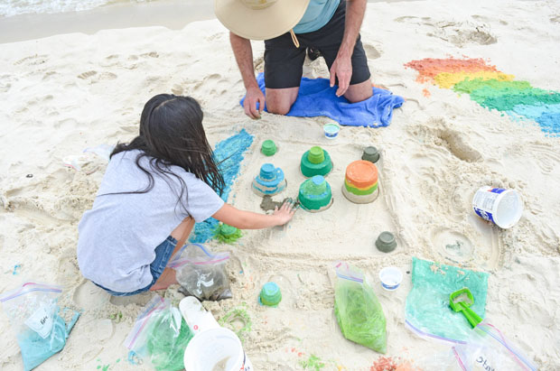 man and daughter showing how to dye sand