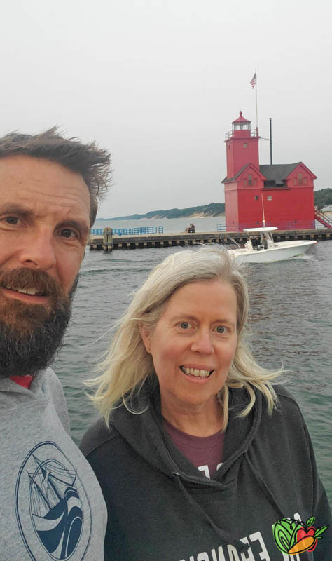 couple posing in front of Big Red Lighthouse in Holland, MI